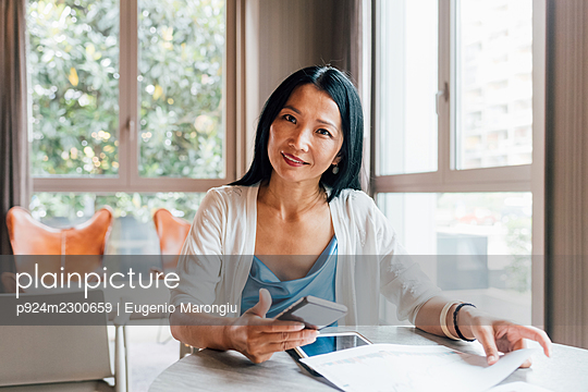 Italy, Portrait of smiling businesswoman at table in creative studio - p924m2300659 by Eugenio Marongiu