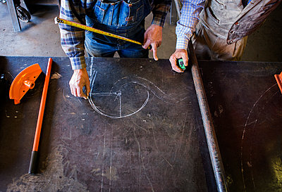 Craftsmen planning and drawing on workbench at factory - p1166m1231598 by Cavan Images
