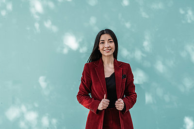 Smiling businesswoman in red blazer standing against turquoise wall - p300m2266401 by COROIMAGE