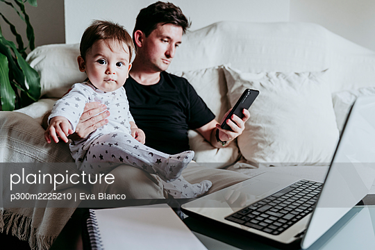 Father using smart phone while holding son sitting on sofa at home - p300m2225210 by Eva Blanco