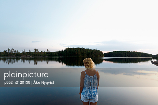 Woman standing by Lake Skiren in Sweden - p352m2120138 by Åke Nyqvist