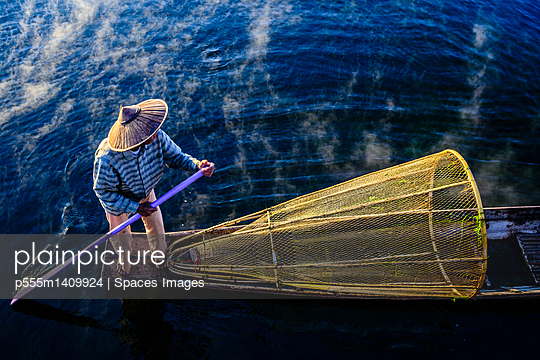 High angle view of Asian fisherman using fishing net in canoe on river