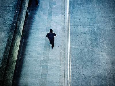 Lone man walking down pavement - p1072m836378 by Neville Mountford-Hoare