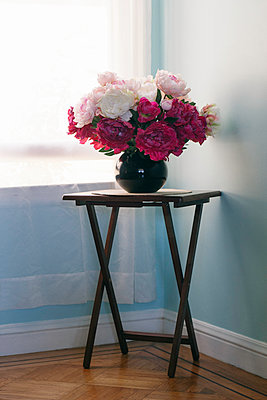 Plastic peonies on corner table at the window - p1106m2182542 by Angela DeCenzo