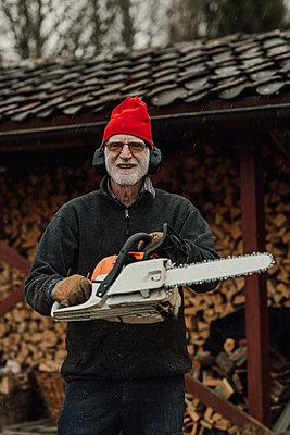 Senior man holding chainsaw - p312m2190969 by Jennifer Nilsson