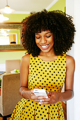 Mixed race woman using cell phone - p555m1413324 by Peathegee Inc