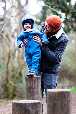 Father and son balancing on wooden pole in park - p795m2192234 by JanJasperKlein
