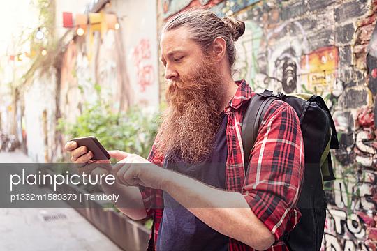 Männlicher Hipster benutzt sein Smartphone - p1332m1589379 von Tamboly