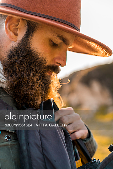 Italy, Sardinia, portrait of bearded hiker with hat and backpack - p300m1581624 von VITTA GALLERY