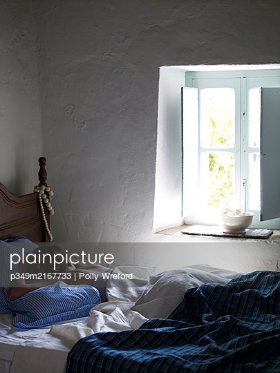 Woman sleeping at open window of Spanish villa - p349m2167733 by Polly Wreford