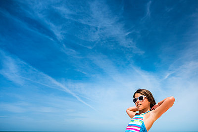 Low angle view of girl in sunglasses against cloudy sky - p1166m1489107 by Cavan Images