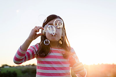 Low angle view of girl blowing bubbles while standing against clear sky at park during sunset - p1166m1576146 by Cavan Images