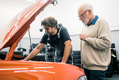 Car mechanic talking to client in workshop - p300m2167395 by Robijn Page