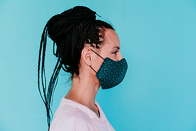 Woman wearing protective face mask with hair bun against turquoise background - p300m2220826 by Eva Blanco