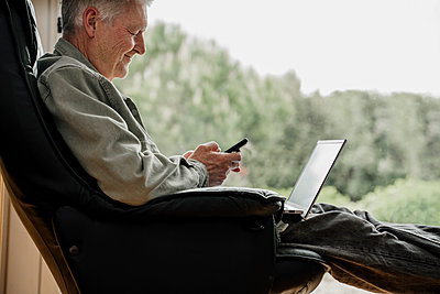 Smiling man using mobile phone on chair at home - p300m2281375 by VITTA GALLERY