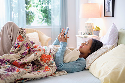 Mixed race woman using cell phone in bed - p555m1306217 by JGI/Tom Grill
