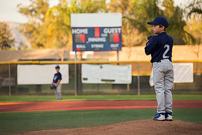 Boy baseball pitcher preparing to throw on baseball field - p924m1404234 by Ian Spanier
