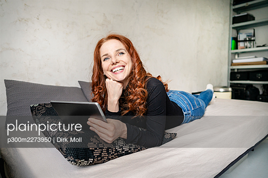 Thoughtful redhead woman with digital tablet lying on sofa while looking away at home - p300m2273950 by Dirk Moll