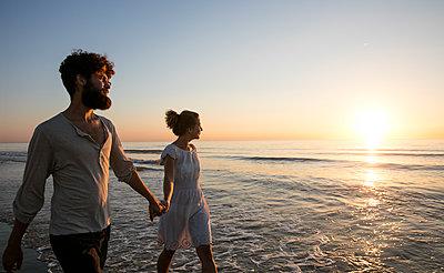 Junges Paar - Sonnenuntergang am Strand - p1212m1168725 von harry + lidy