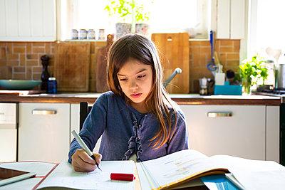 Girl doing homework in kitchen at home - p300m2198584 by Larissa Veronesi
