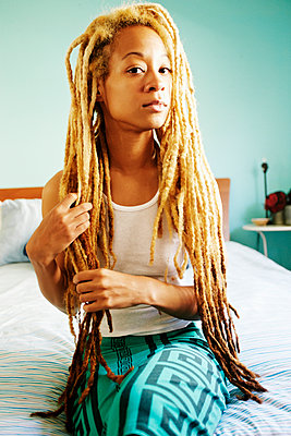 Black woman with dreadlocks sitting on bed - p555m1411302 by Peathegee Inc