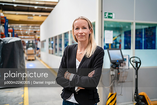 Smiling blond businesswoman with arms crossed standing in industry - p300m2240305 von Daniel Ingold