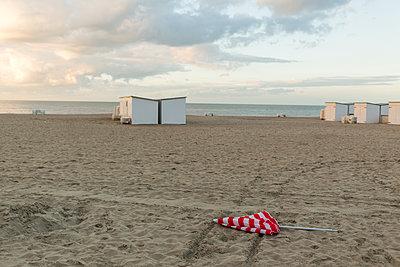 Verlorener Sonnenschirm und Strandhütten - p1271m1548329 von Maurice Kohl