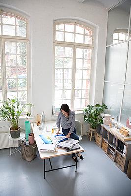 Woman working at desk in a loft office - p300m2012529 von Florian Küttler