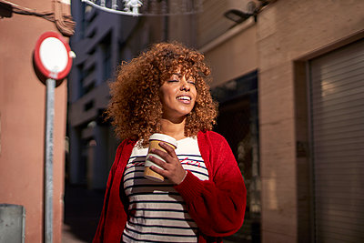 Beautiful woman with disposable coffee cup smiling while standing against street - p300m2257352 by Veam