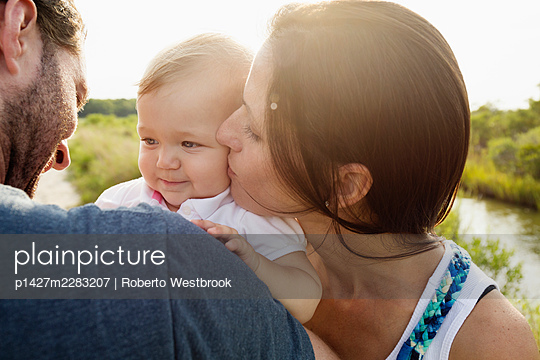 Over shoulder view of mid adult parents kissing baby daughter on riverside - p1427m2283207 by Roberto Westbrook