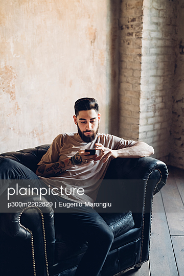 Young man sitting in armchair in a loft using smartphone - p300m2202829 by Eugenio Marongiu