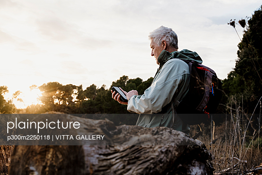 Senior man sitting on wooden log while using smart phone during sunset - p300m2250118 by VITTA GALLERY