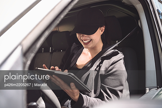 Smiling female driver using digital tablet in truck - p426m2205267 by Maskot