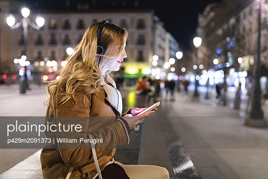 Young woman listening to headphones and using smartphone in city square at night, Madrid, Spain - p429m2091373 by William Perugini