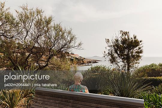 Ältere Frau liest auf Parkank - p432m2064441 von mia takahara