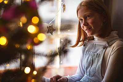 Cute girl sitting on window sill and looking at christmas tree - p1315m1518540 by Wavebreak