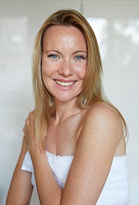 Portrait of a smiling woman, wrapped in towel - p300m2043027 von Philipp Nemenz