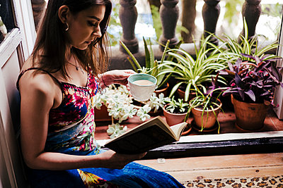 Woman holding cup while reading book by balcony at home - p300m2202513 by Eva Blanco