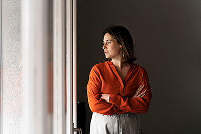 Businesswoman with arms crossed looking through window at home - p300m2206522 by VITTA GALLERY