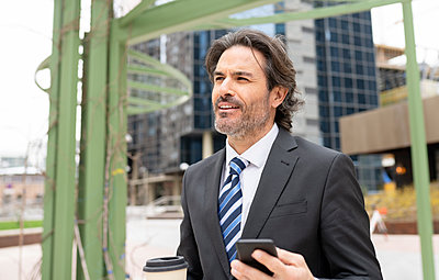Smiling male professional looking away while holding coffee cup and mobile phone - p300m2275222 by Jose Carlos Ichiro