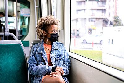 Mid adult woman wearing mask looking through tram window - p300m2277421 by Rafael Fernandez Torres