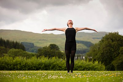 Mature woman practicing yoga position with arms open in field - p429m1054465f by Leon Harris