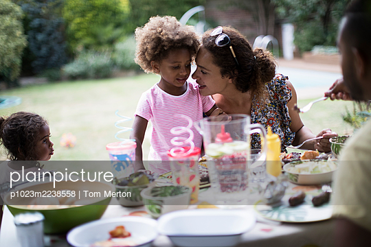 Mother and daughter enjoying backyard barbecue at patio table - p1023m2238558 by Tom Merton