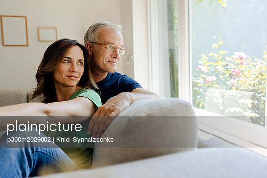 Smiling mature couple sitting on couch at home looking out of window - p300m2029802 von Kniel Synnatzschke