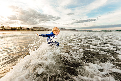 Young child jumping waves at a beach in New Zealand - p1166m2137619 by Cavan Images