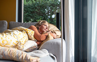 Thoughtful woman looking through window while lying on sofa at home - p300m2240042 by Bernd Friedel