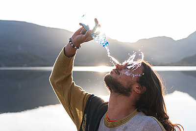 Man pouring water on face with bottle near lake during sunny day - p300m2282002 by Josu Acosta