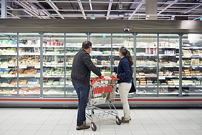 Mature couple looking at food on display at refrigerated section in supermarket - p426m1451856 by Maskot