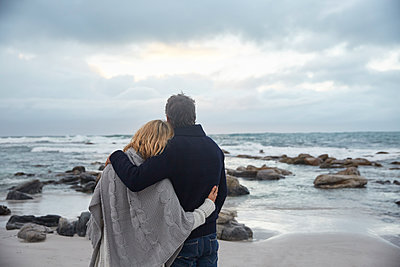 Serene affectionate couple hugging on winter beach looking at ocean - p1023m1217905 by Ryan Lees