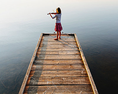 A ten year old girl playing the violin at dawn on a wooden dock. - p1100m876045f by Paul Edmondson